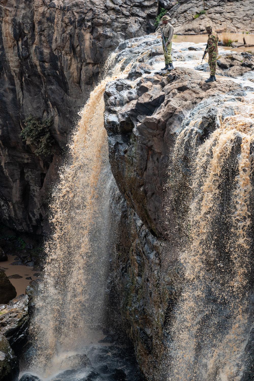Wildlife rangers on patrol at a waterfall along the Ewaso Nyiro river in the Laikipia region of Kenya