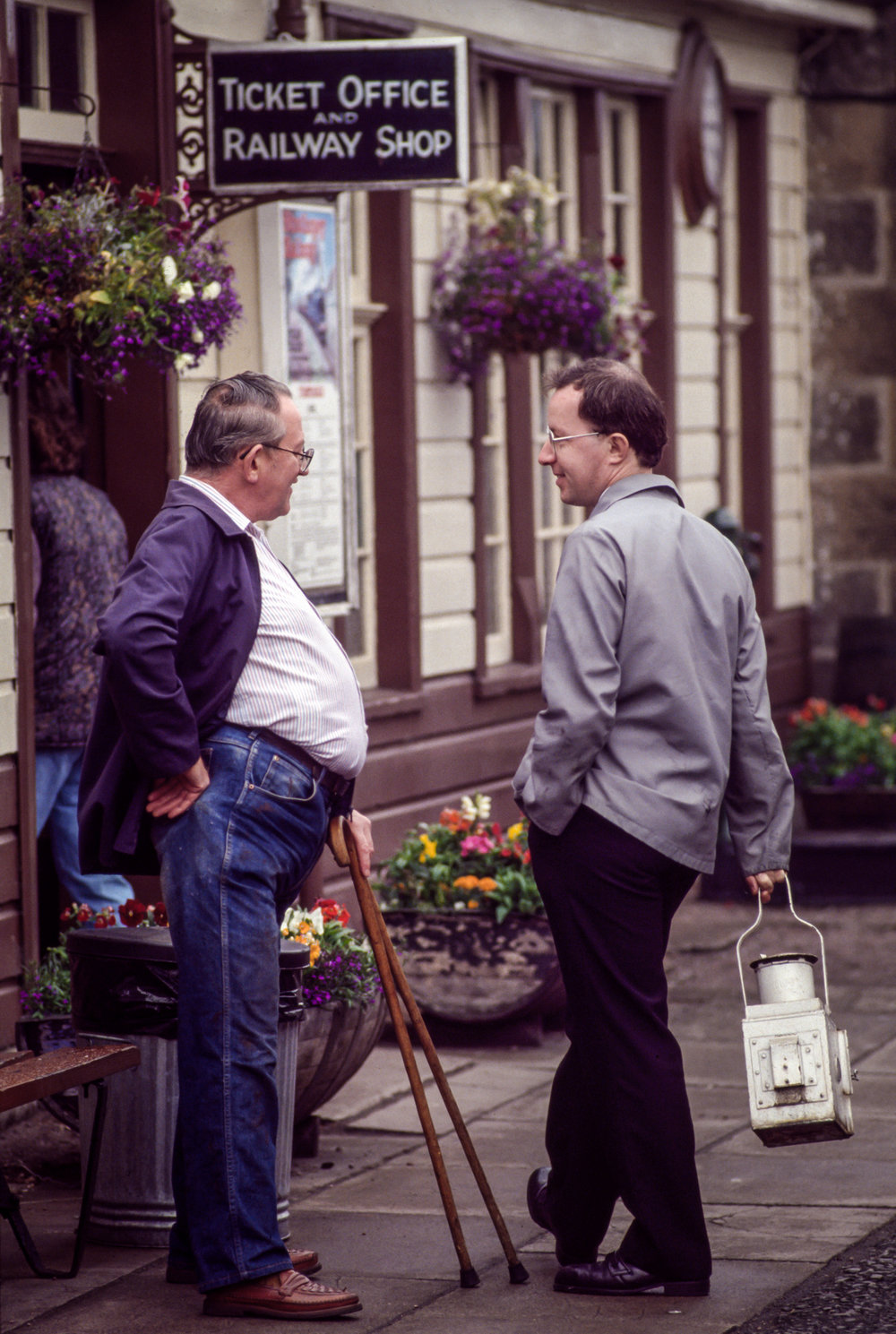 A ticket salesman and conductor talk outside the Strathspey Railway station in Aviemore, Scotland
