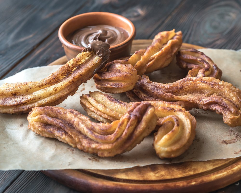 Churros Con Chocolate - Normally eaten for breakfast, Churros are a fried dough that can either be thin or long and thick. Sugar is often sprinkled on top and most usually dipped in a thick hot chocolate,