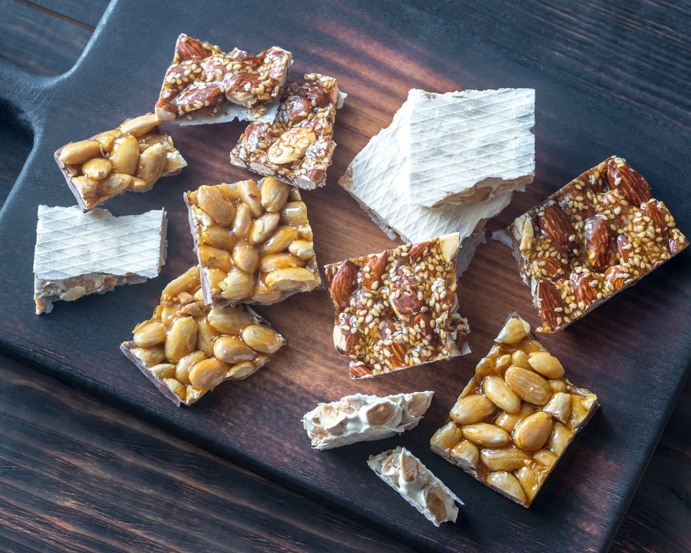 Turrón - This nougat confection is typically made of honey, sugar, and egg white, with toasted almonds or other nuts, and usually shaped into either a rectangular tablet or a round cake.