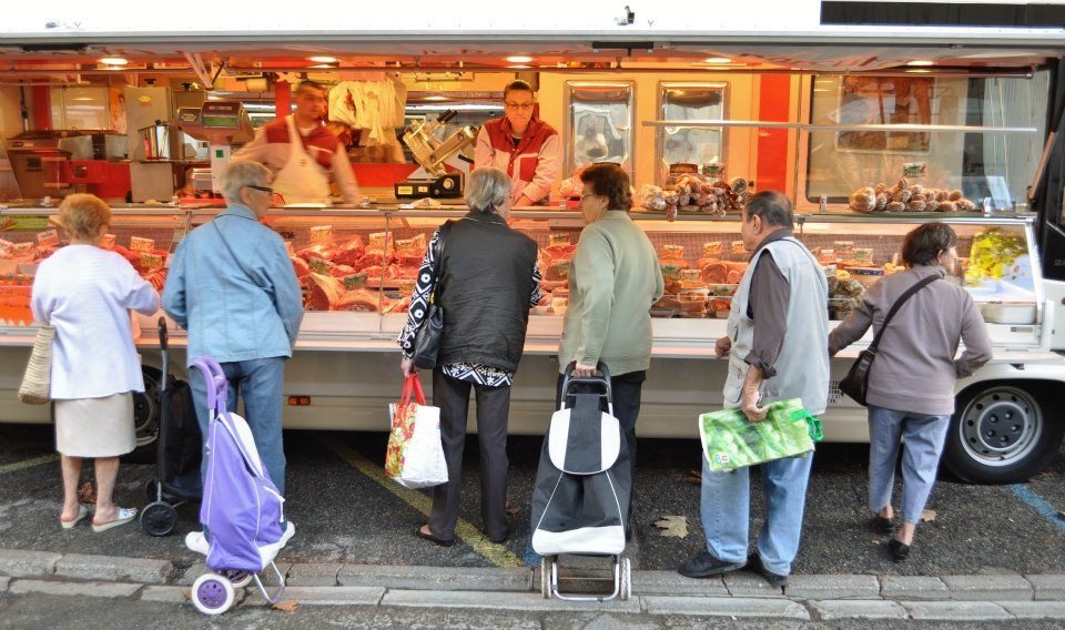 Customers on line at the mobile butcher shop at the Vaison La Romaine Tuesday market