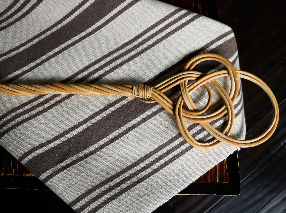 A beige striped rug with a Finnish rug beater