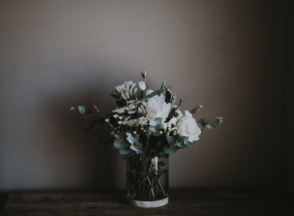 Natural looking greenery and white flowers on a rustic table