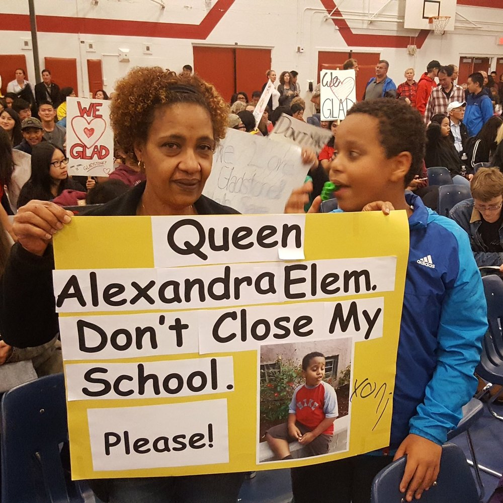 A mom and her child hold up a poster at a VSB committee meeting urging the board not to close their school.   Morgane was DPAC chair at the time and organized parents to successfully prevent the closure of 12 schools everyone knew were desperately needed.  Photo: Morgane Oger
