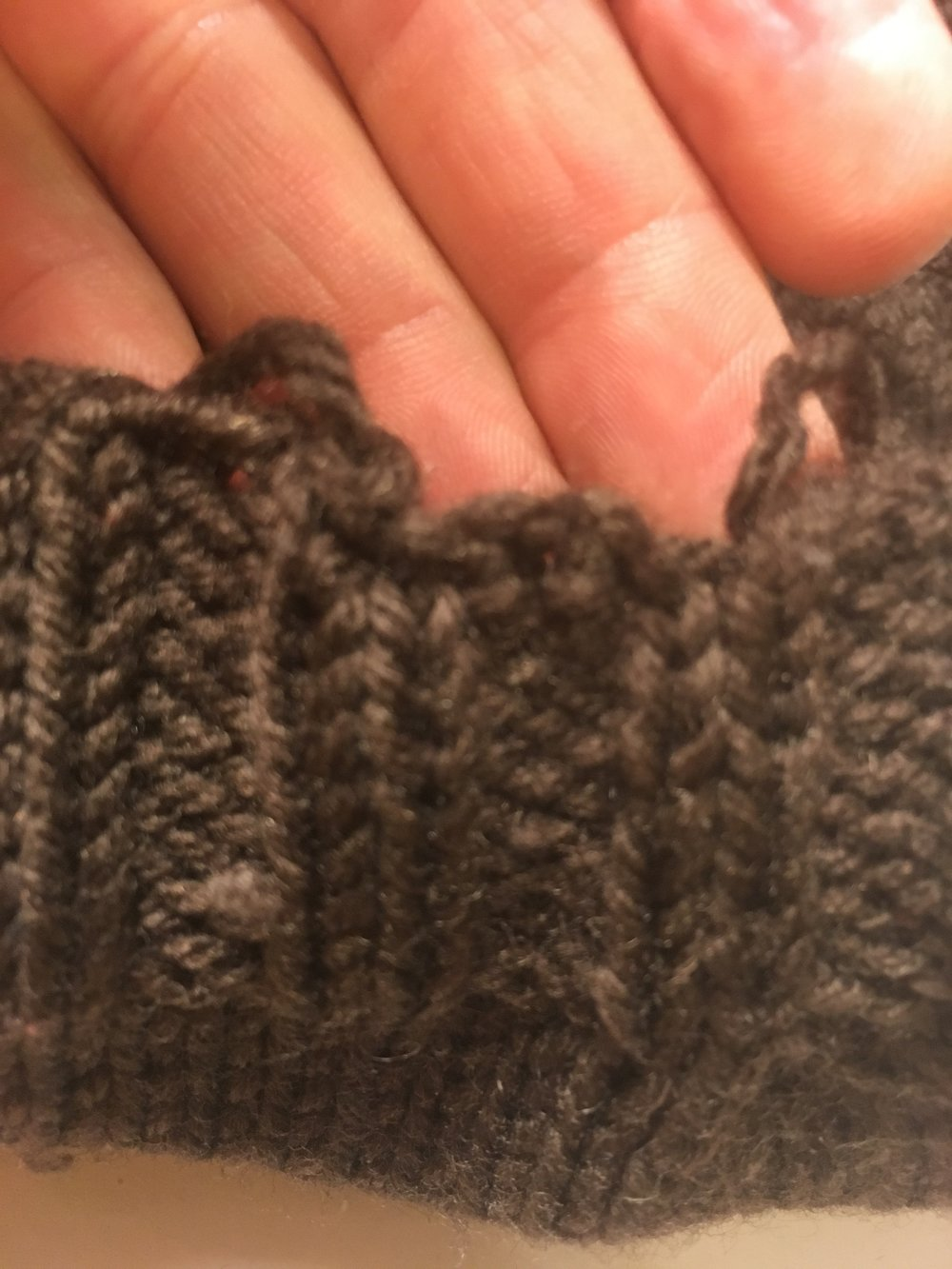 The sewn bind off edge was considerably lower. Note the loose yarns of the original tubular bind off on each side. I secured those later down the inside of columns of ribbing.