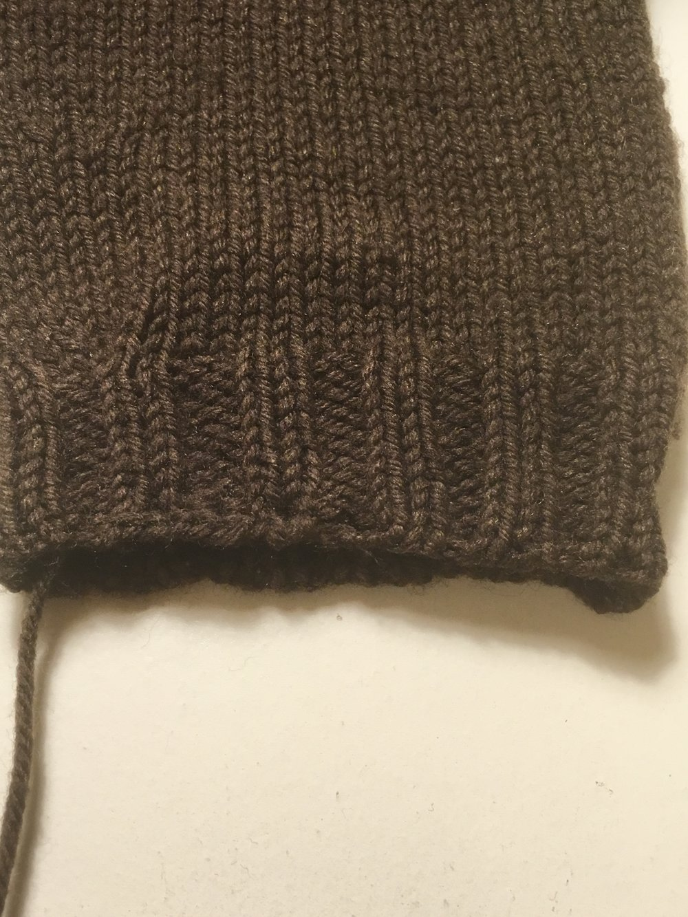 The final edge still shows the horizontal direction of the sewn bindoff versus the curved edge of the original tubular bind-off, but it still looks really good overall and most people won't even notice the repair.