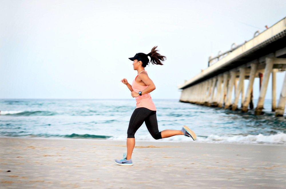 woman in sportswear running on the beach