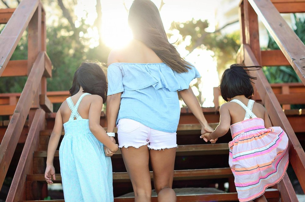 mom walking with her daughters with coordinated outfits