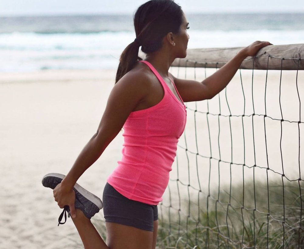 woman in sportswear stretching on the beach