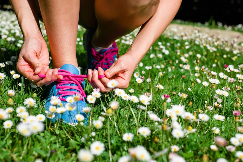 person tying their pink shoe lace while on a field of white flowers