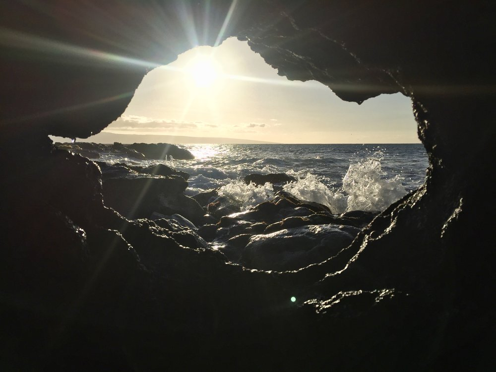 The ocean framed by lava on a beach in Maui (photo by:  @thelotuspage )