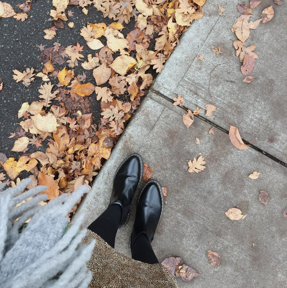 A woman standing on the sidewalk beside fall leave wearing a leopard skirt Doc Marten bianca boots and an urban outfitters scarf female lifestyle blogger Canadian blogger