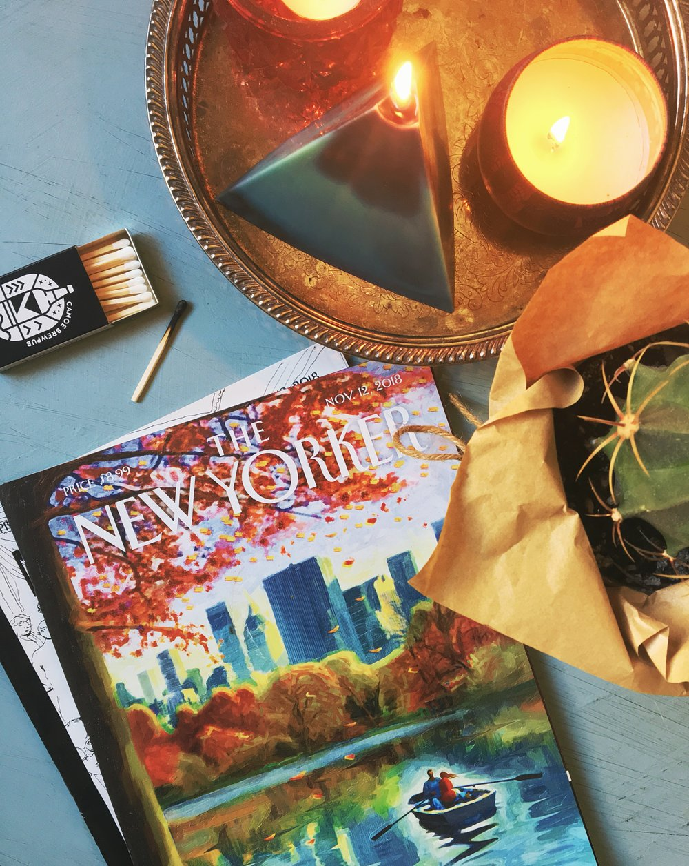 The New Yorker magazine sitting on a coffee table beside a book of matches a pyramid candle and a cactus female lifestyle blogger freelance writer Canadian lifestyle blogger feminist blogger