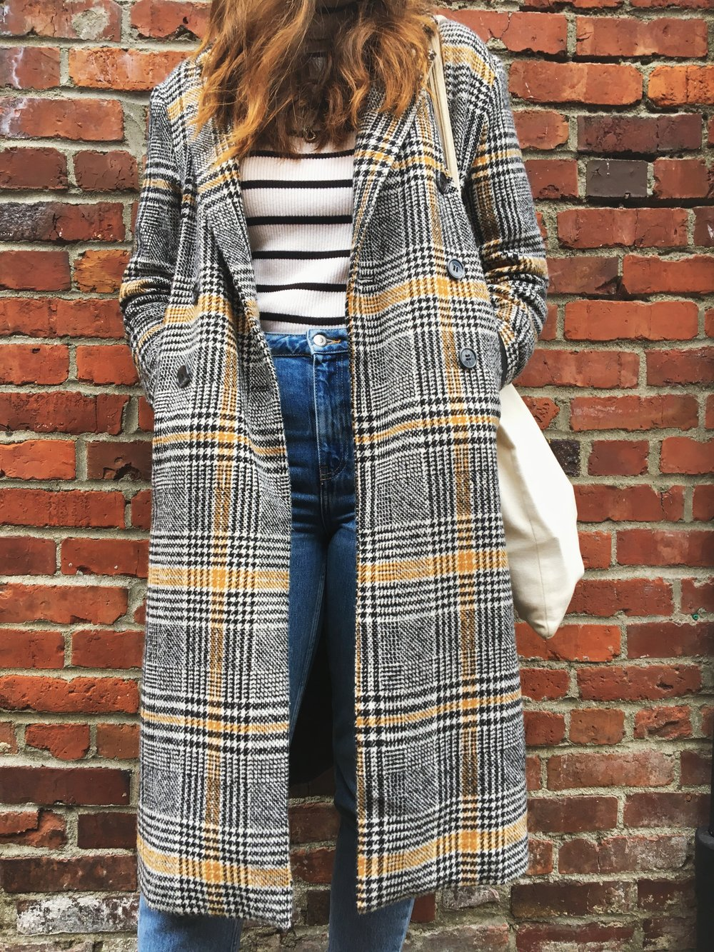 woman standing against brick wall wearing a pink knit toque a plaid coat striped turtle neck topshop mom jeans and doc marten boots lifestyle blogger victoria blogger canadian blogger