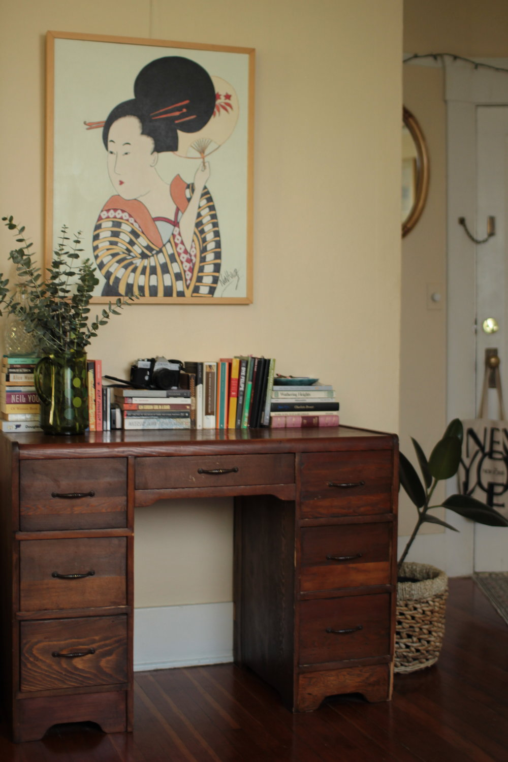 a wooden antique desk with stacks of books on top and a large antique painting with a rubber plant next to it The States of Georgia lifestyle blog Canadian blogger feminist blogger