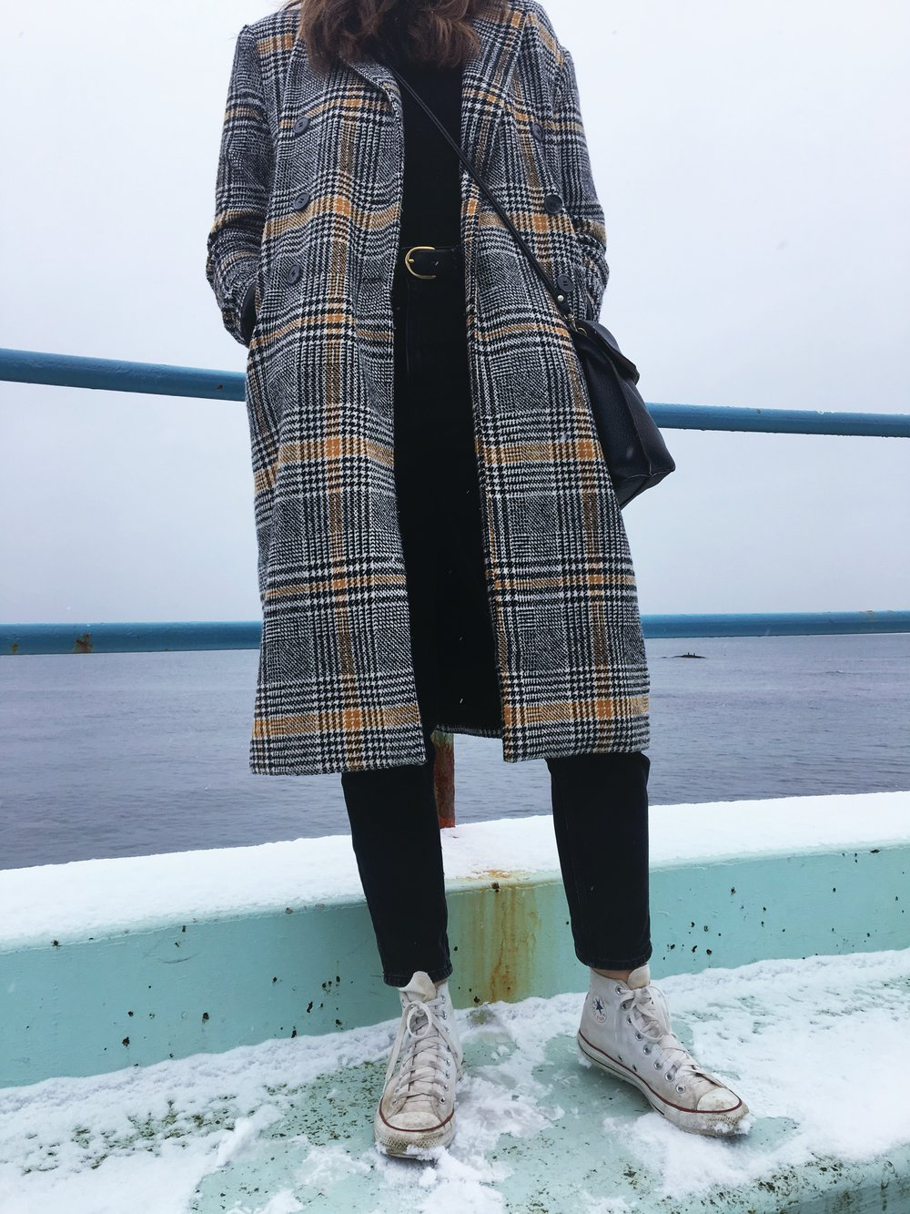 a woman wearing a baker boy cap and a plaid coat standing on a blue bench in front of the ocean The States of Georgia lifestyle blog Canadian lifestyle blog writing blog Why I Gave Up Trying to be Chill