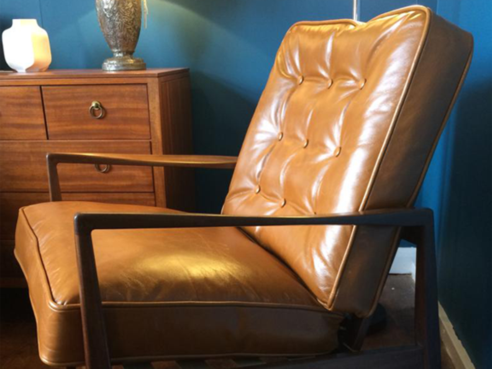 Restored 1960s Italian teak framed lounge chair with tan hide cushions.