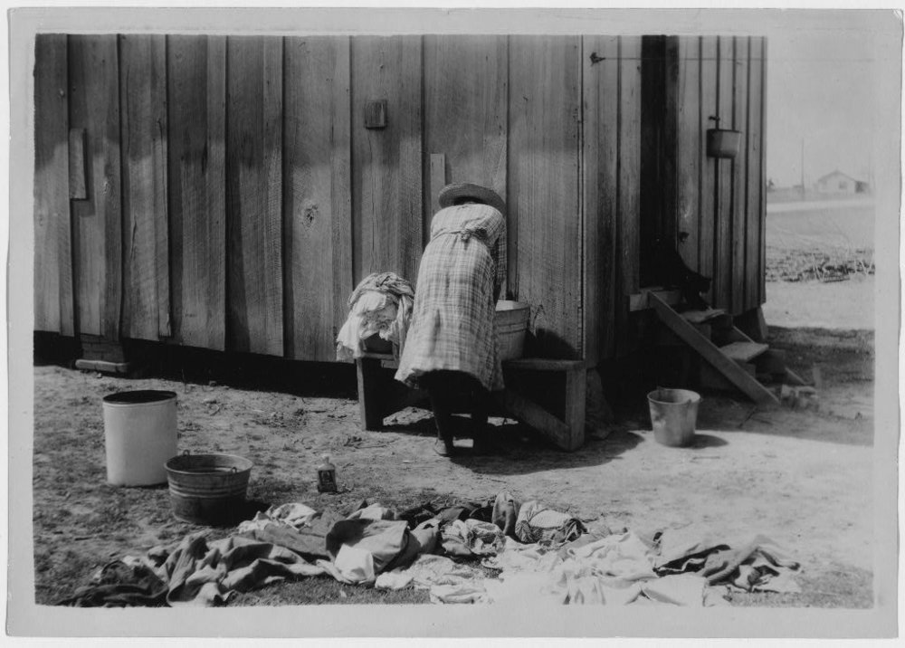 Rear view of woman washing clothes ca. between 1937 and 1938 via Library of Congress.