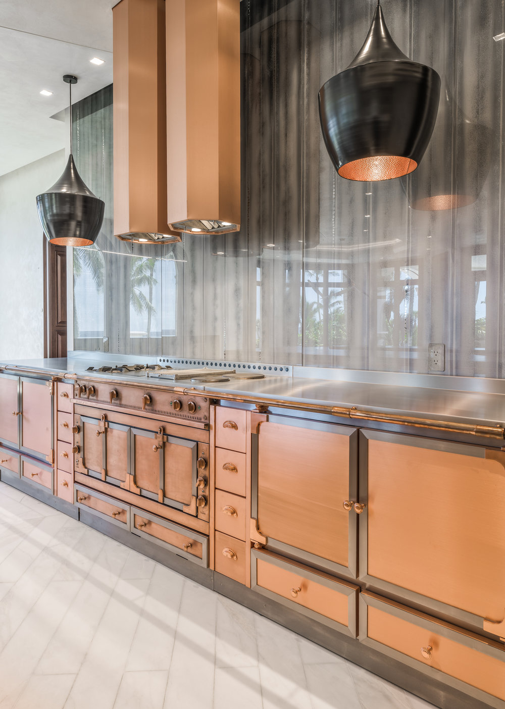 Private Beachfront Estate Kitchen Feature Wall Inspired by an iconic La Cornue range, designer Chad Jensen commissioned Copper and Stainless-Steel cabinetry handcrafted by French artisans. Balanced by a custom designed Copper hood, Tom Dixon pendants, and artist painted eglomise glass panels.