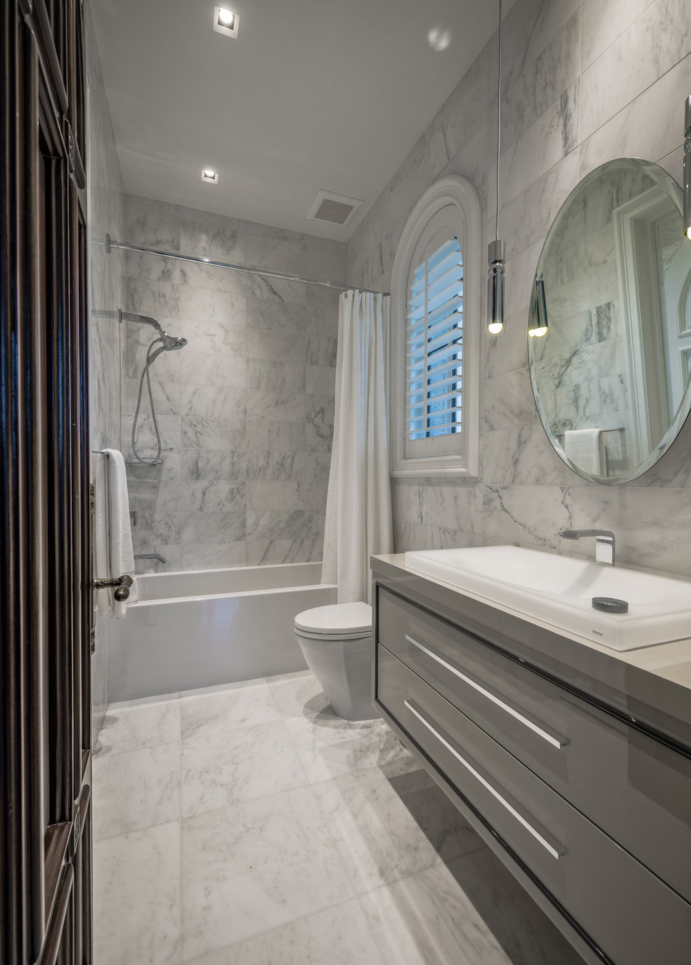 Private Beachfront Estate Guest Bathroom Premium custom bath with exquisite features throughout including Statuary marble, custom high-gloss vanity cabinet, and an illuminated LED sink.