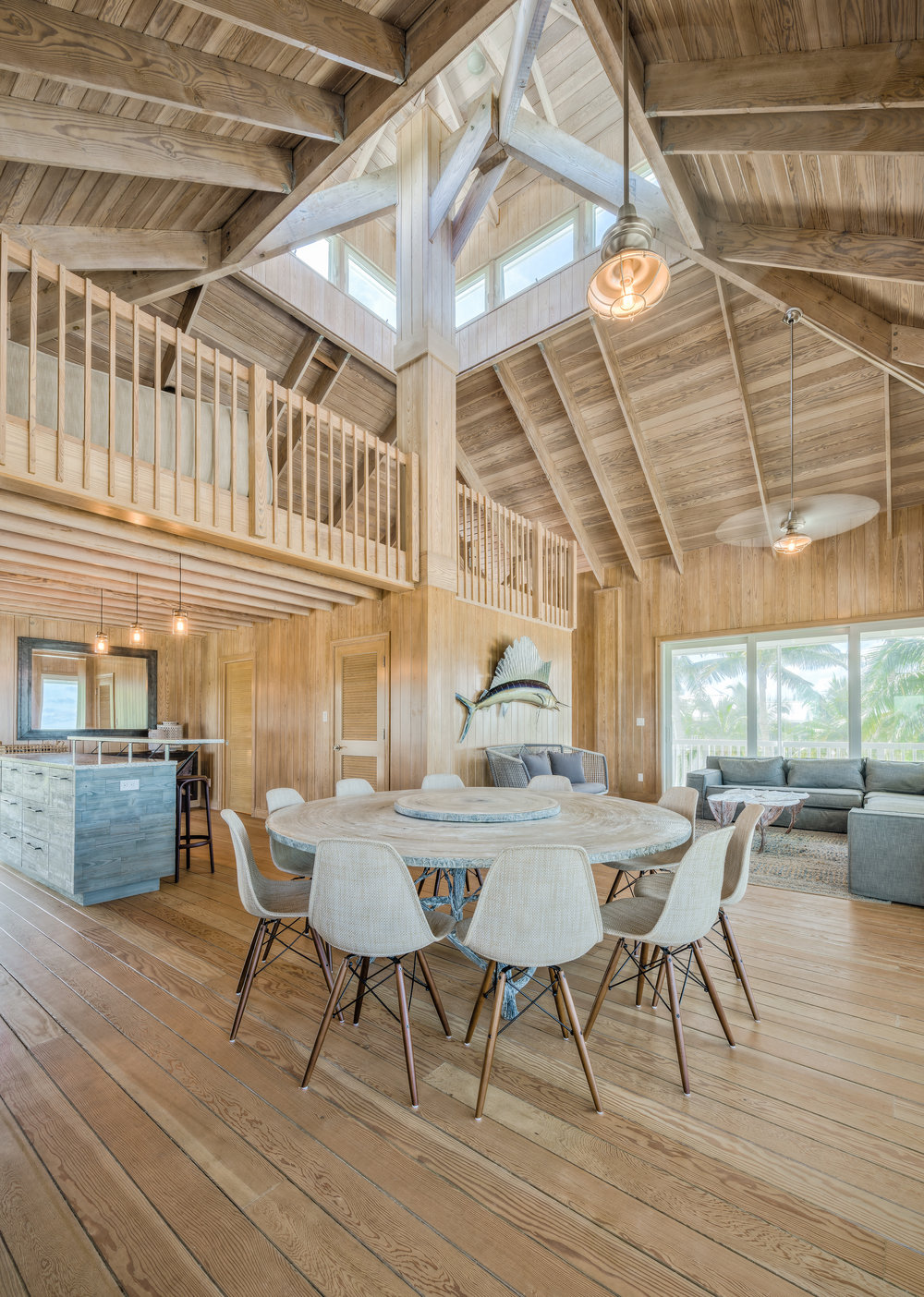Private Island Beach House Kitchen This architecturally redesigned space was expanded to achieve an open-concept floor plan for entertaining. Custom weathered wood cabinetry, vintage industrial hardware, and artist commissioned sculpted furnishings.