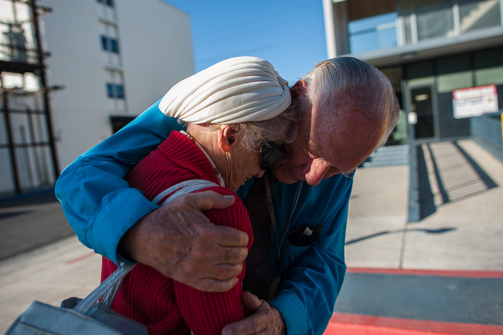 Will comforts Adina who does not want him to leave, as they stand near the entrance of the retirement home where she lives.