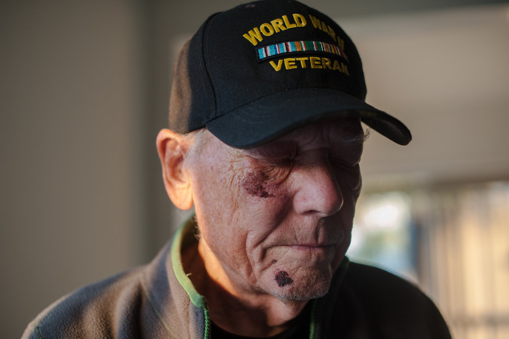 Will stands with his eyes closed, wearing his World War II Veteran cap.