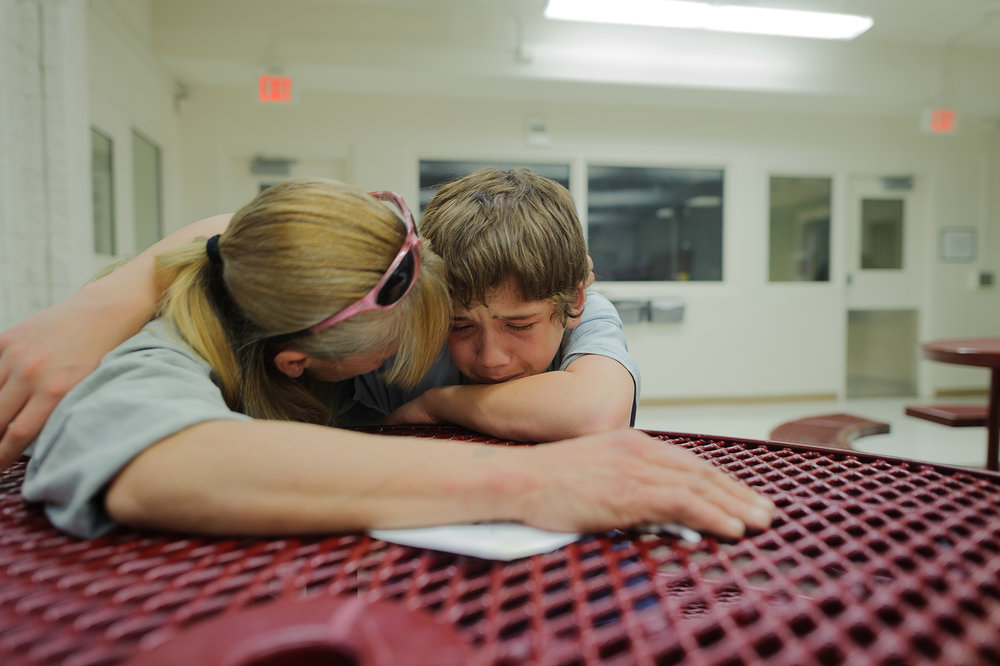 "Vinny, age 13, cries during a visit with his mom, Eve, at the juvenile detention center. He says, ""get me out mom, just get me out,"" 2012."