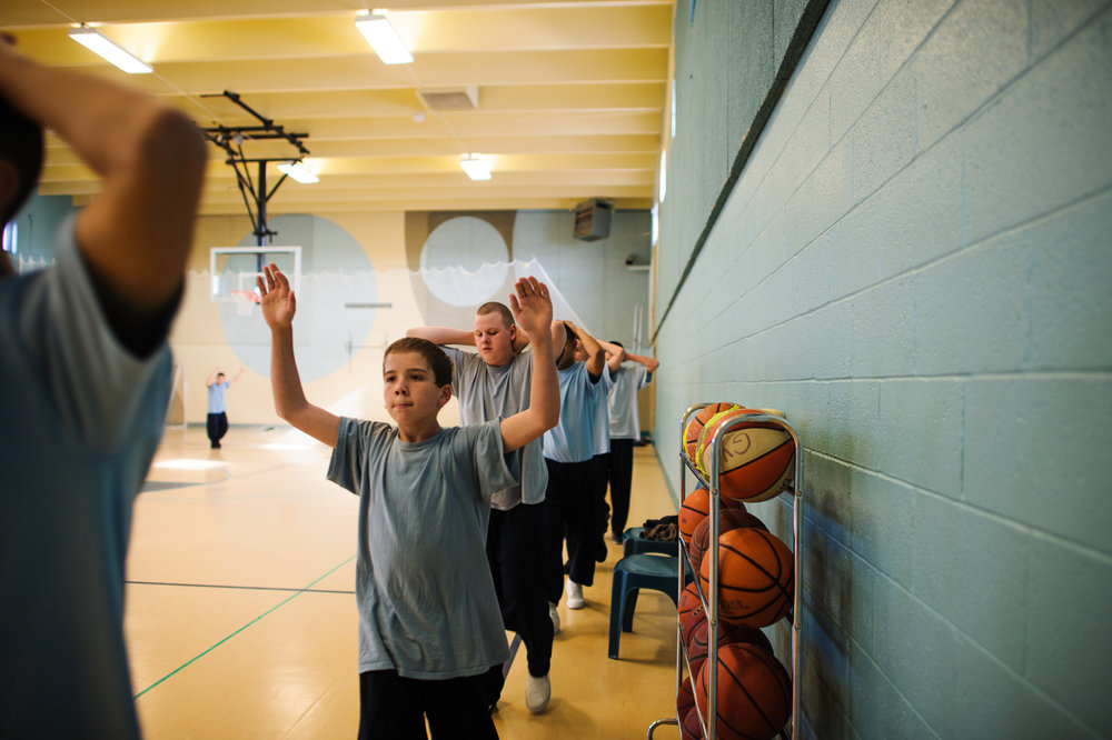 Vinny, age 13, walks with hands up as boys march in a circle inside the gym at the juvenile detention center, 2012.