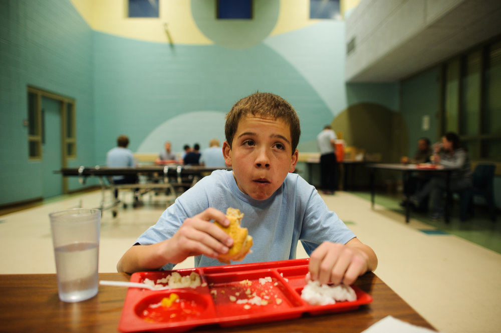 Vinny, age 13, eats his first meal in the detention center cafeteria, 2012.