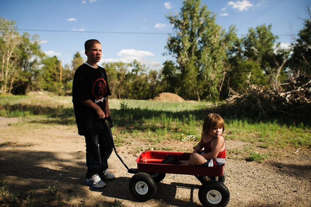 Vinny, age 13, pulls Elycia in a wheelbarrow during a family visit, 2012.