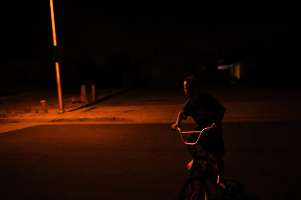 Michael, age 7, rides a bike at night, 2012.