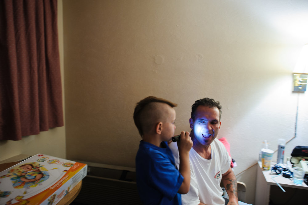 Michael, age 7, points a flash light at his dad, Eddie's, face during a family visit inside David's motel room, 2012.