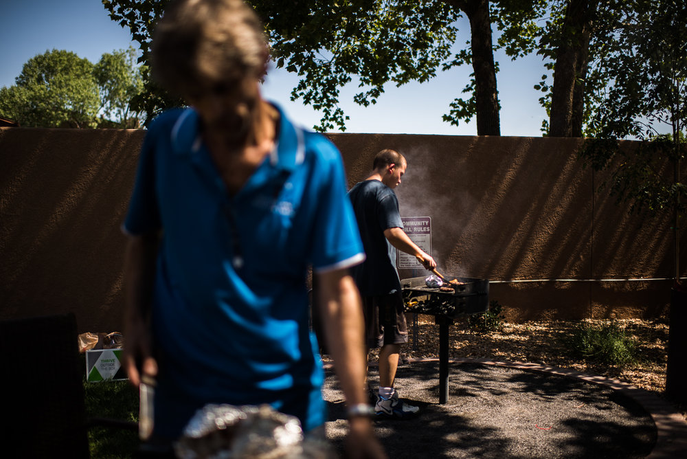 Vinny, age 18, grills meat while a family friend, Jerry, prepares the lunch table in the recreation area of the apartment complex where Jerry lives, 2017.