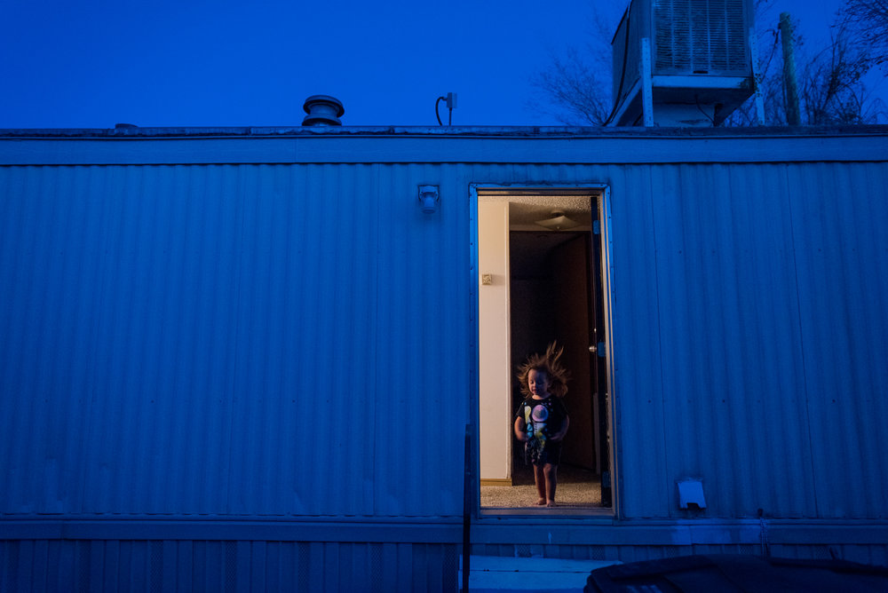 Jordyn, age 2, stands in the doorway of Eve's trailer, 2018.