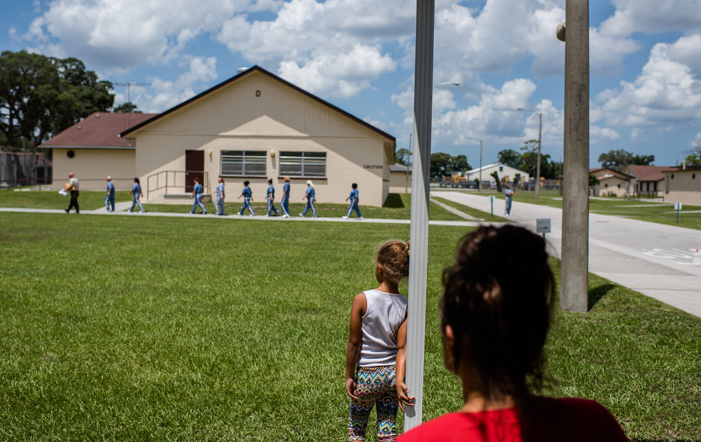 A girl watches a line of incarcerated women walk towards their housing unit at the Hernando Correctional Institution in Brooksville, Florida.