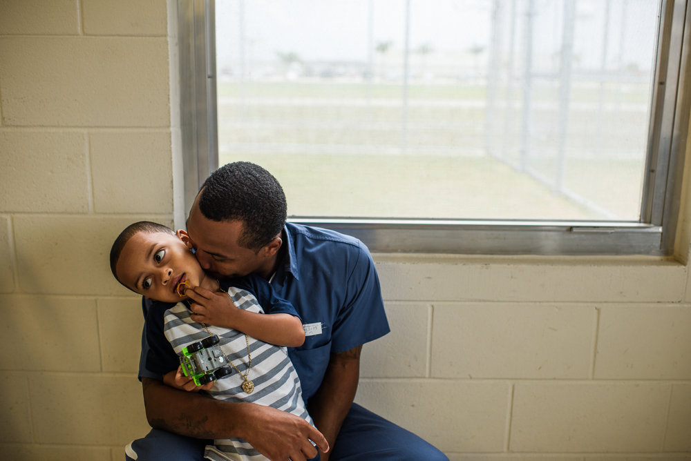 "Arnaldo, age 28, kisses his son Joseph, age 4, during a visit at the Okeechobee Correctional Institution in Okeechobee, Florida, where Arnaldo is incarcerated. ""My son asks me, 'When are you getting out of time-out?' I tell him the reality of where he is. The other dads tell their kids that this is a school. I tell my son where I am."""