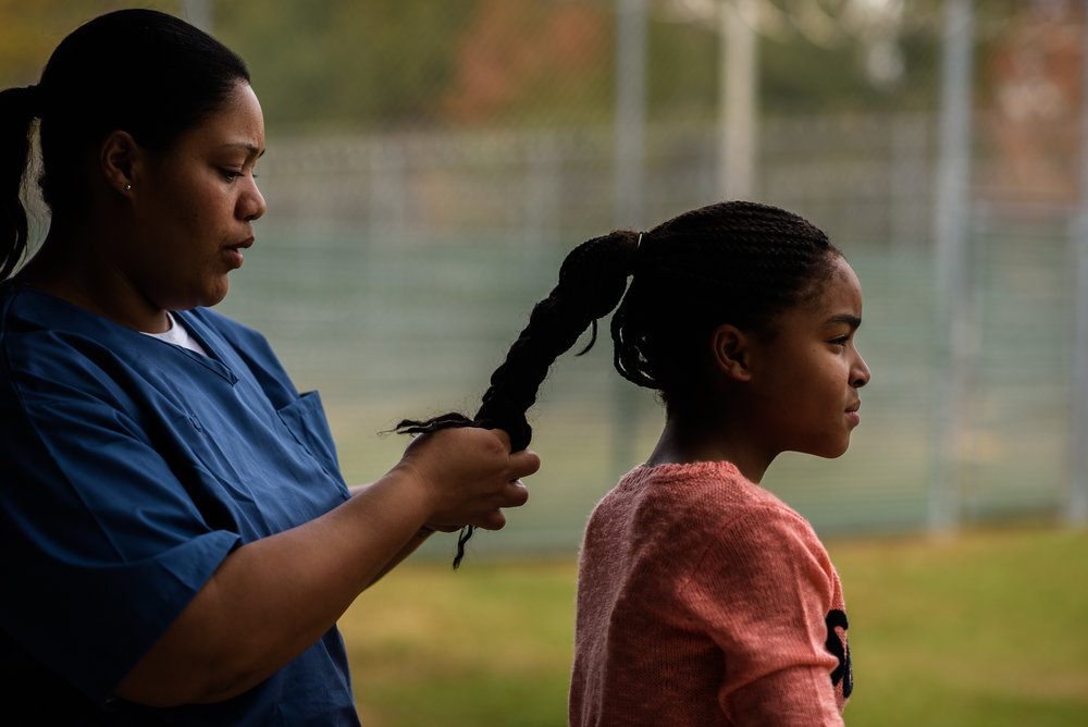 A mother braids her daughter's hair in the recreation yard at the Lowell Correctional Institution in Ocala, Florida.