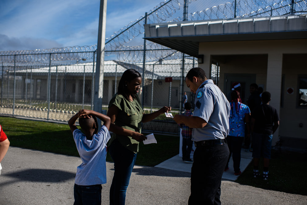 A woman and her son are checked in before a father-child visit at the Everglades Reentry Center in Miami, Florida.