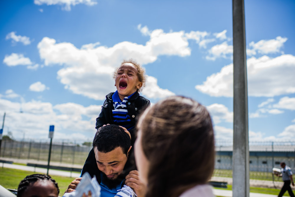 A boy cries while sitting on his father's shoulders upon exiting the Lowell Correctional Institution in Ocala, Florida, where his mom is incarcerated.