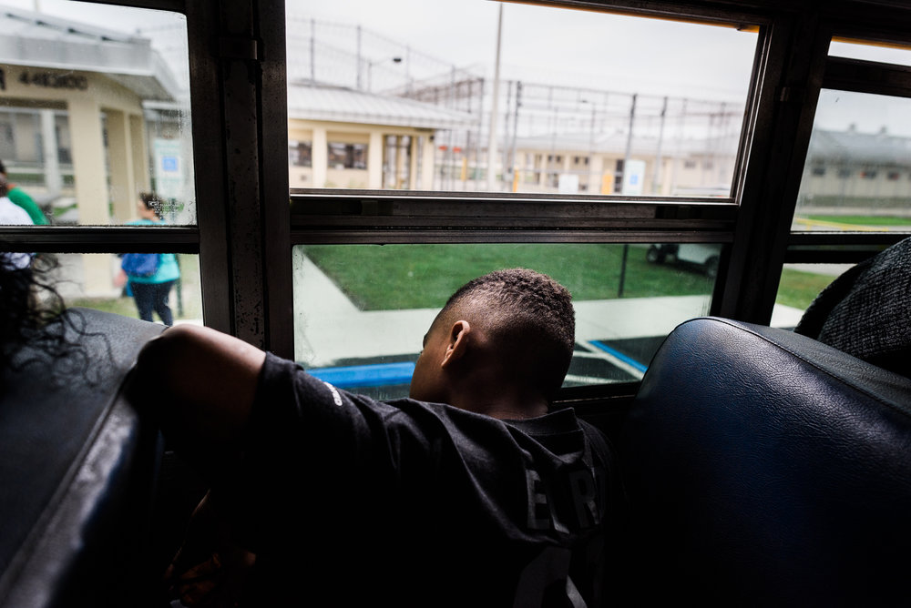 Rodarian, age 9, sits on the bus after seeing his father at the Everglades Reentry Center in Miami, Florida.