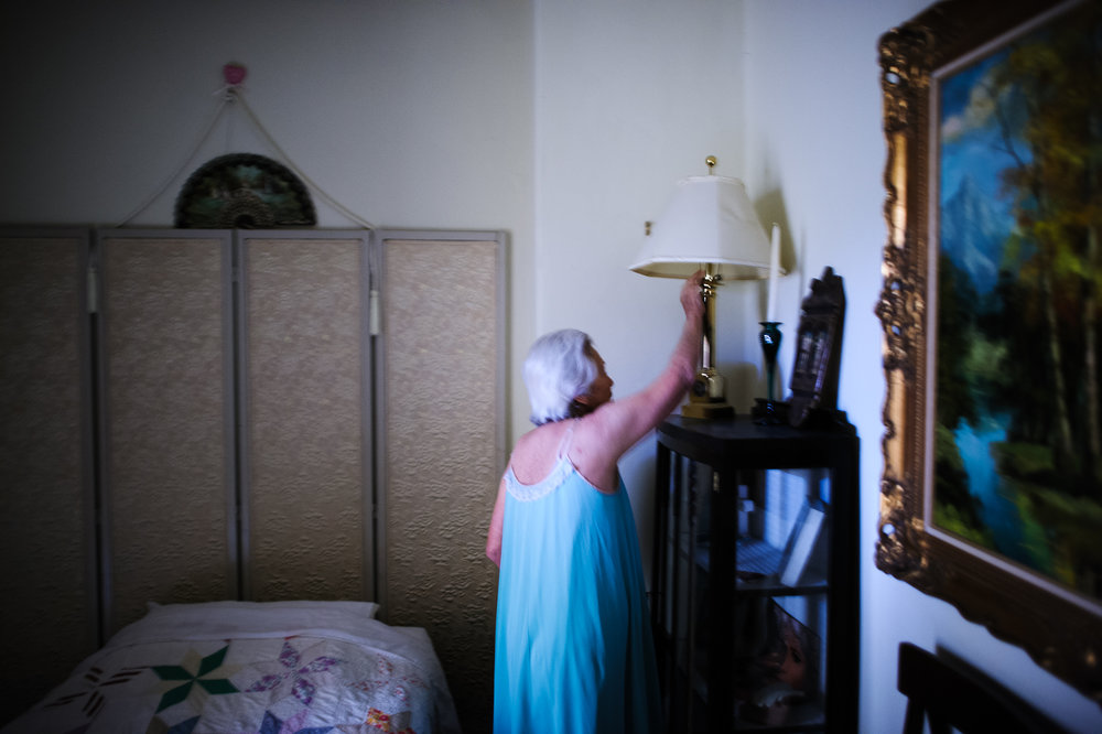 Bianca, age 84, turns on the light in her apartment at the retirement home at night, 2009.