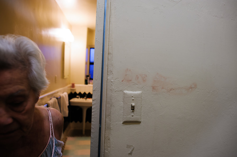 Bianca, age 85, walks passed words she wrote on her wall in lipstick, 2010.