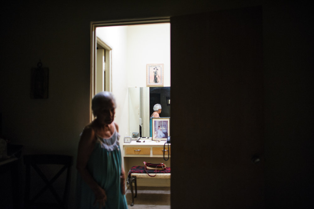 Bianca, age 86, stands in her apartment at night, 2011.