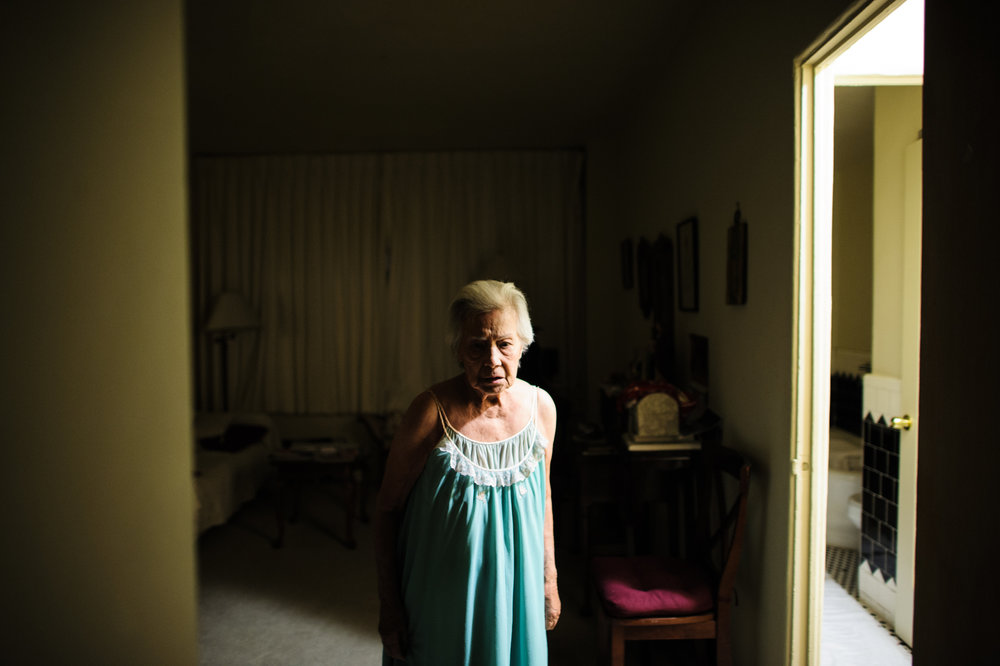 Bianca, age 86, stands her apartment at night, looking at the front door in fear that someone will come in, 2011.