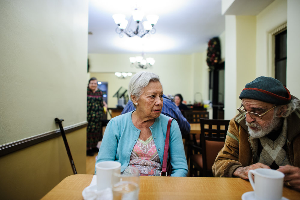 Bianca, age 86, sits with Bill during dinner hour at the retirement home, 2011.