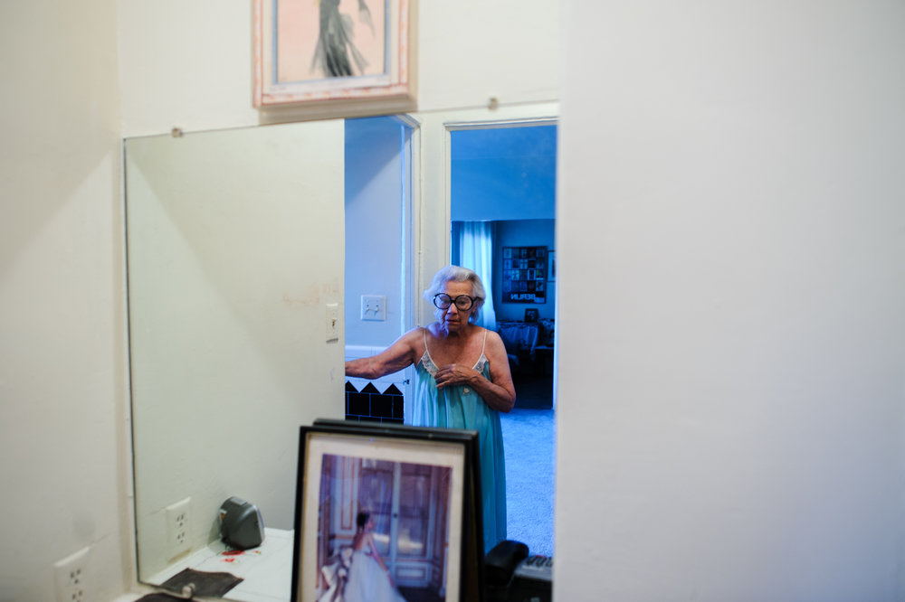 Bianca, age 85, wears her signature glasses and nightgown in front of her mirror, 2010.
