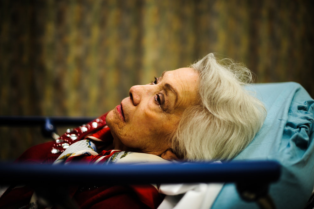 Bianca, age 88, lies on a bed in the emergency room after a fall, 2013.
