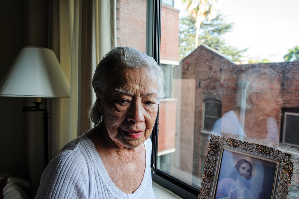 Bianca, age 85, stands by her window in the afternoon, 2010.