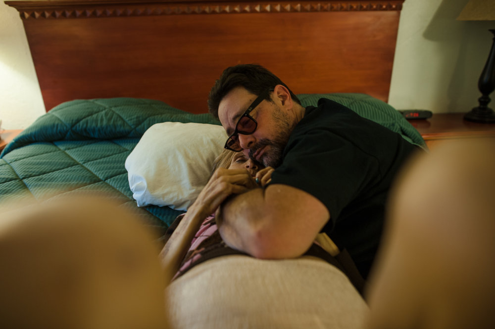 Rosie and Adam embrace on the bed at the motel where they are staying during a vacation to Palm Springs, California.